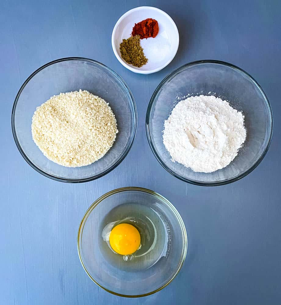 flour, breadcrumbs, an egg, and seasoning in separate bowls
