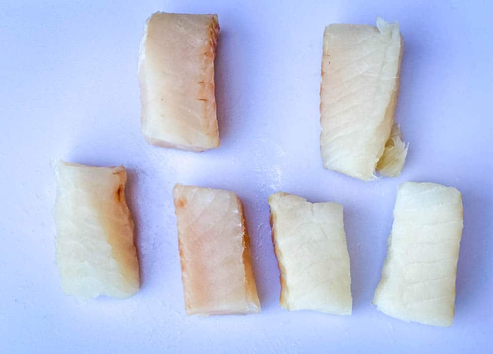 fresh cod fillets on a cutting board