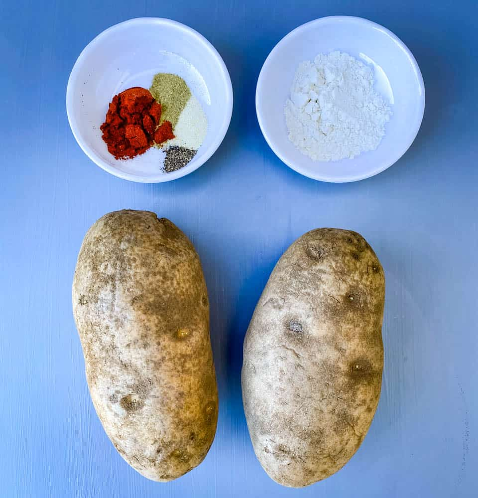 2 russet potatoes on a flat surface with flour and seasoning