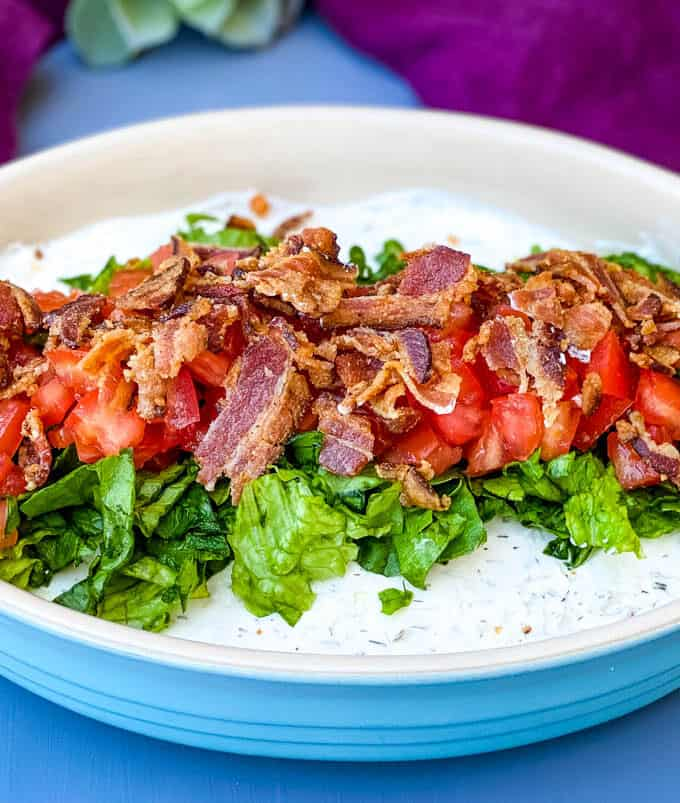 BLT dip with lettuce, bacon, and tomatoes in a blue serving dish