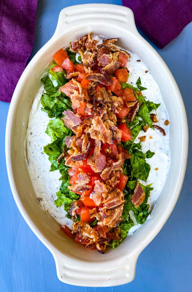 BLT dip with lettuce, bacon, and tomatoes in a serving dish