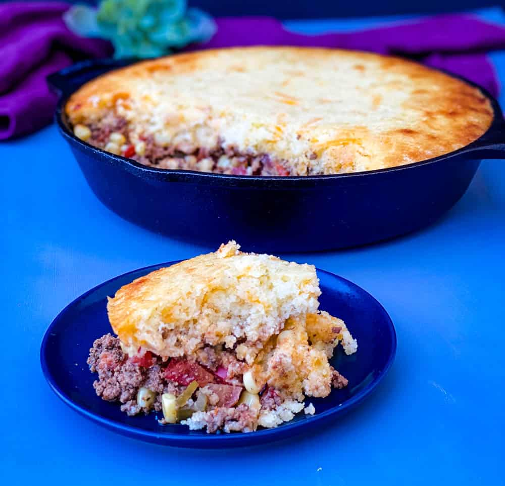 slice of tamale pie and tamale pie in a cast iron skillet