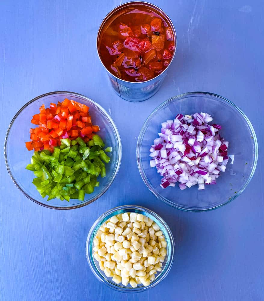 diced tomatoes, red pepper, green peppers, chopped onions, and corn in separate bowls