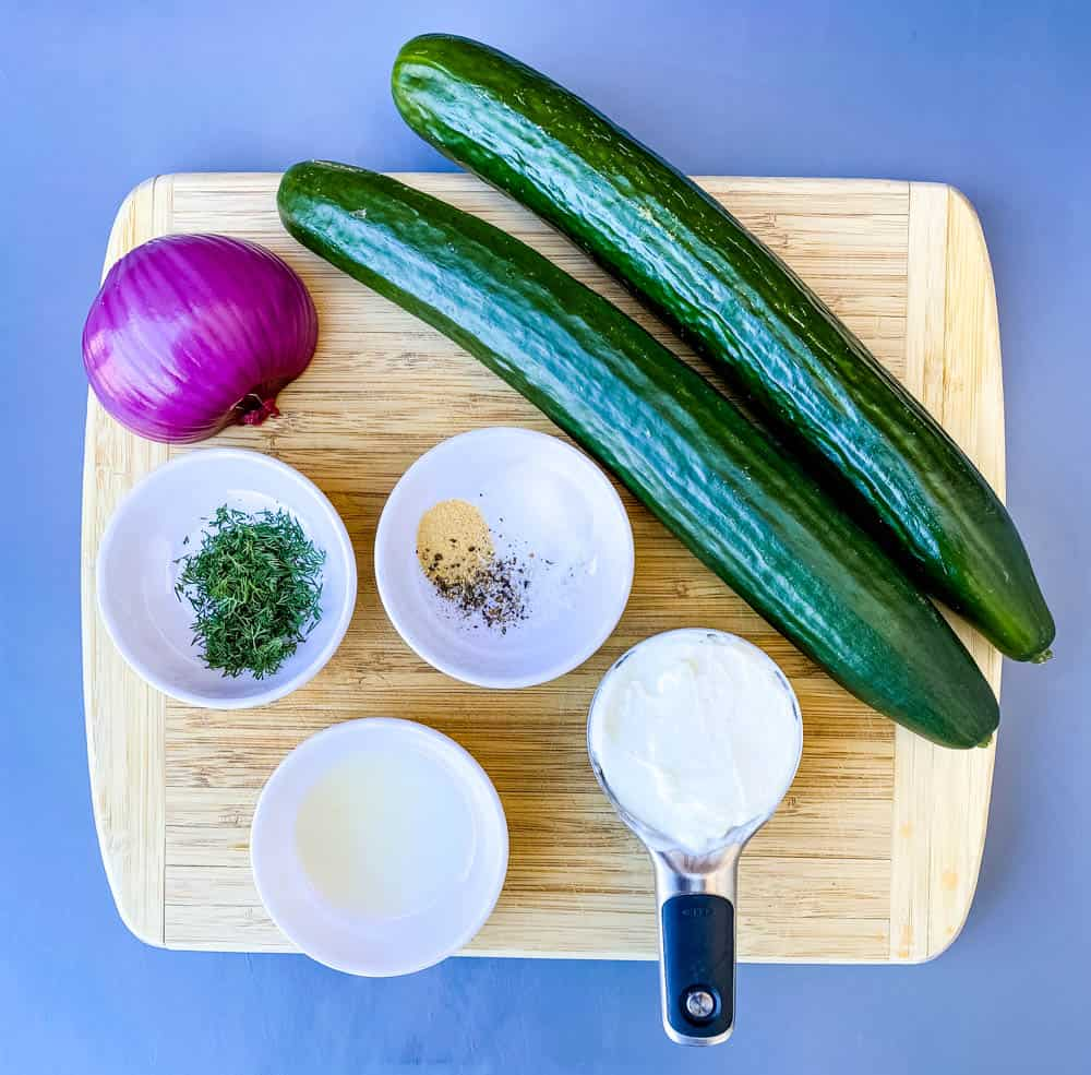 fresh cucumber and a red onion on a bamboo cutting board with a cup of Greek yogurt, fresh dill, seasoning, and lemon juice in separate bowls