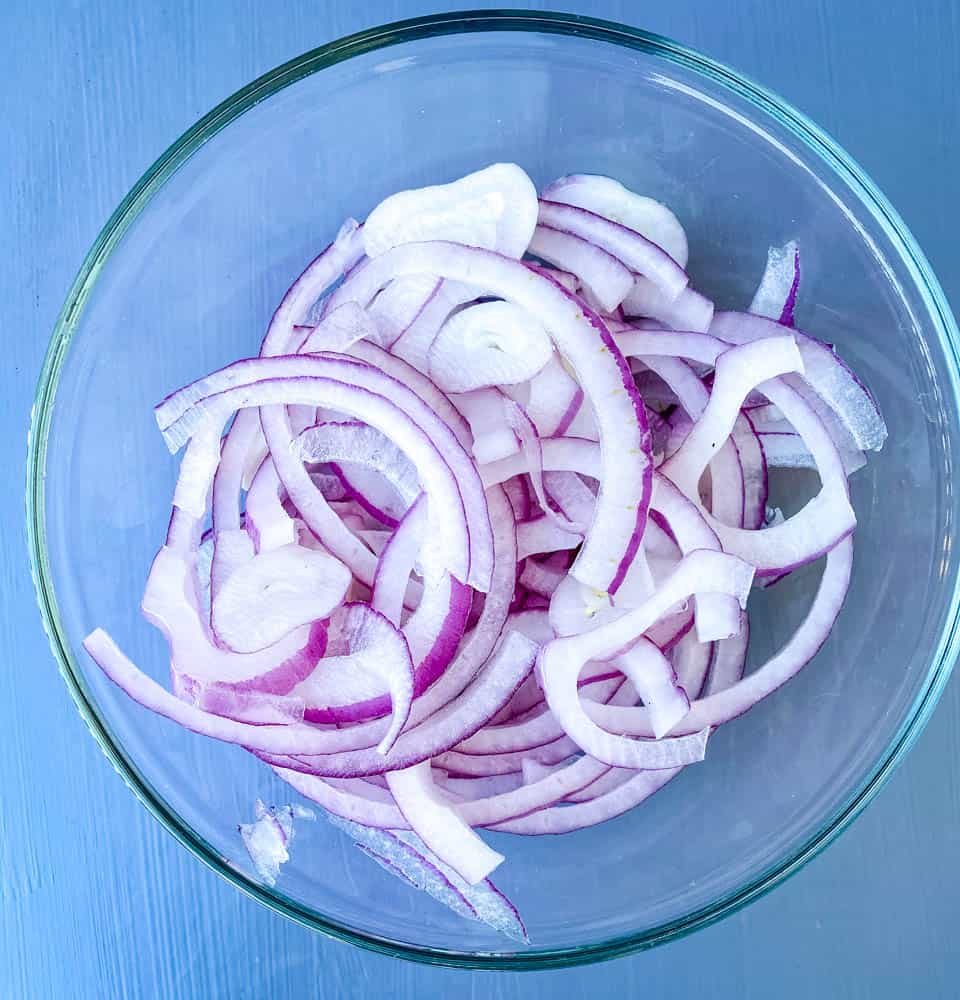 thinly sliced onions in a glass bowl