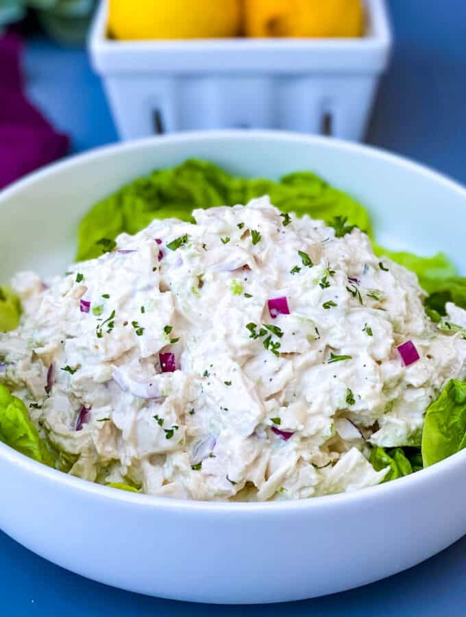 keto chicken salad on a bed of lettuce in a white bowl