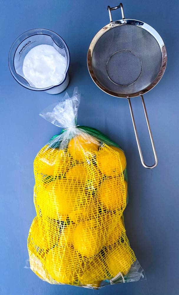 fresh lemons, sweetener, and a strainer on a flat surface