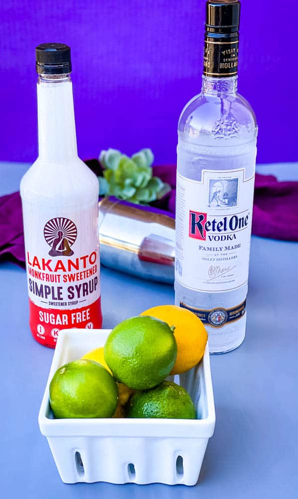 simple syrup, vodka, and fresh limes on a flat surface