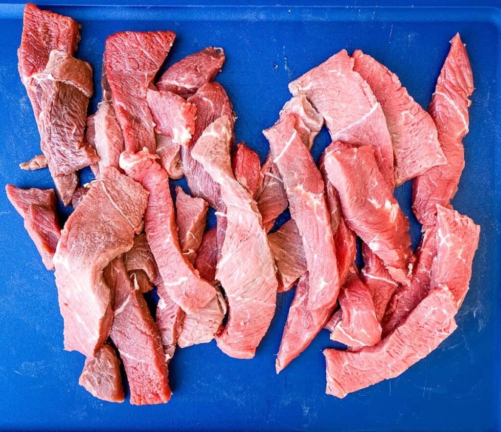 raw slices of sirloin tip steak on a cutting board