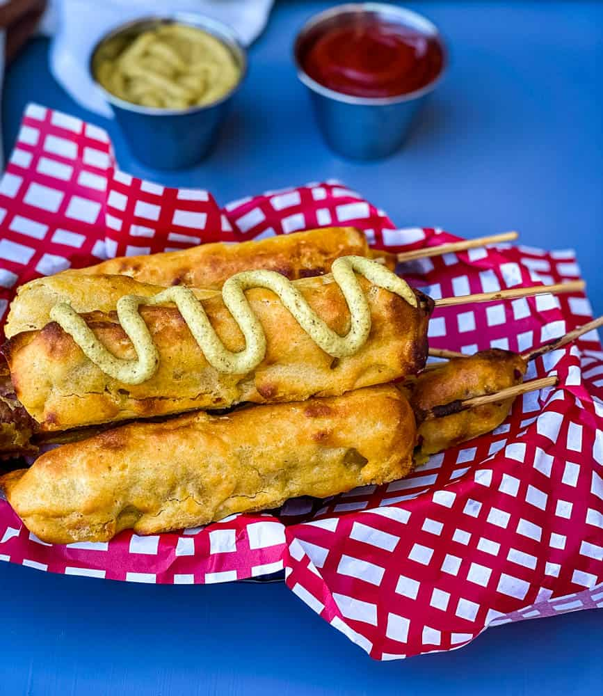 air fryer corn dogs in a basket with a red and white napkin