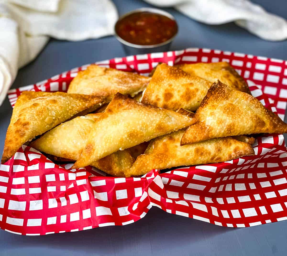 air fryer wontons in a basket with red wrapping