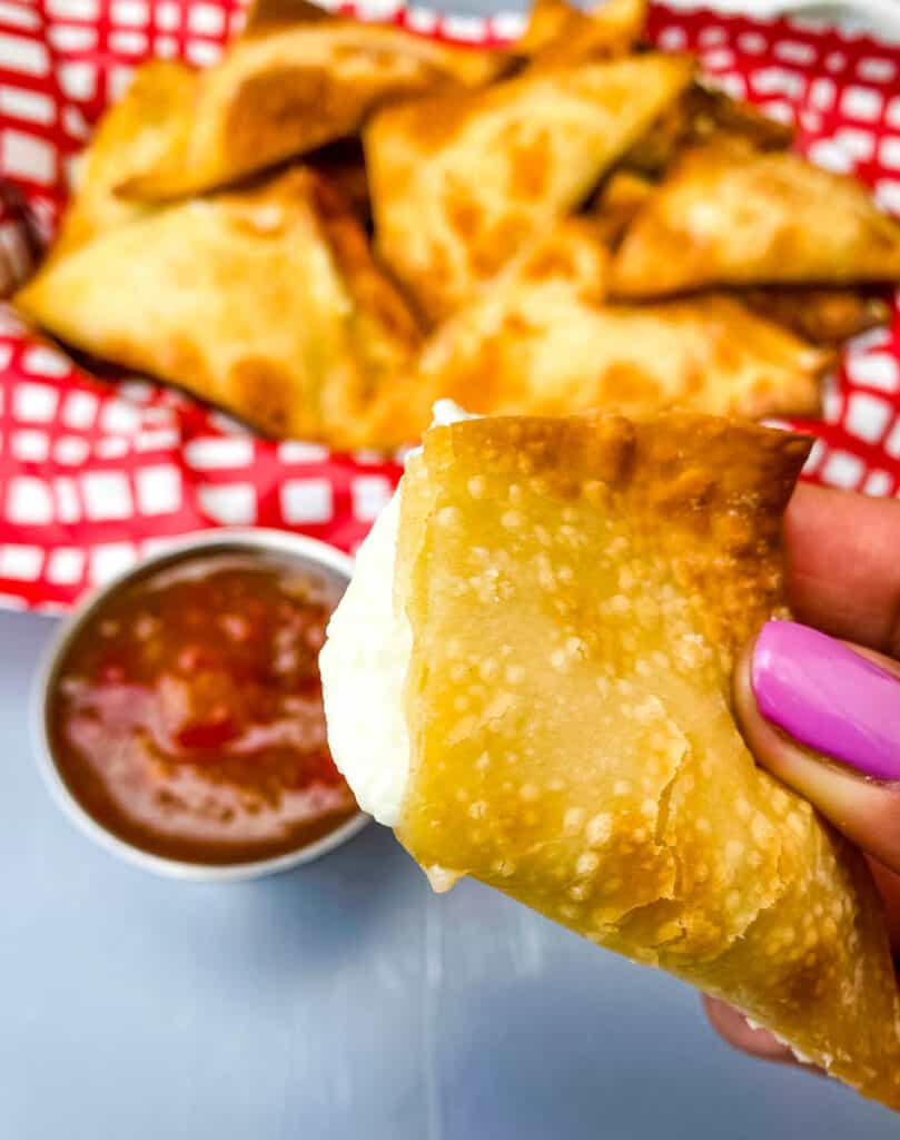 person holding air fryer wonton with cream cheese filling