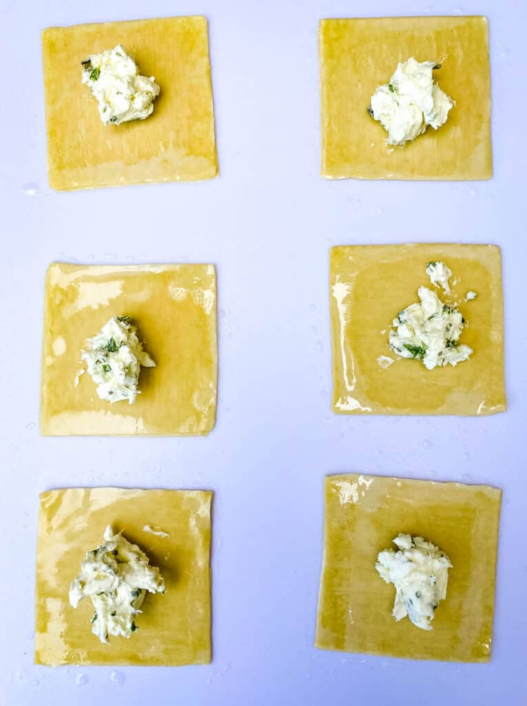 wonton wrappers with cream cheese filling on a white cutting board