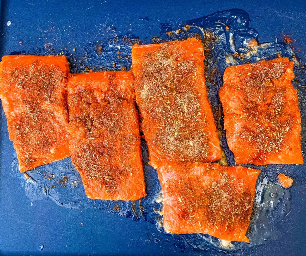 raw and seasoned salmon on a cutting board