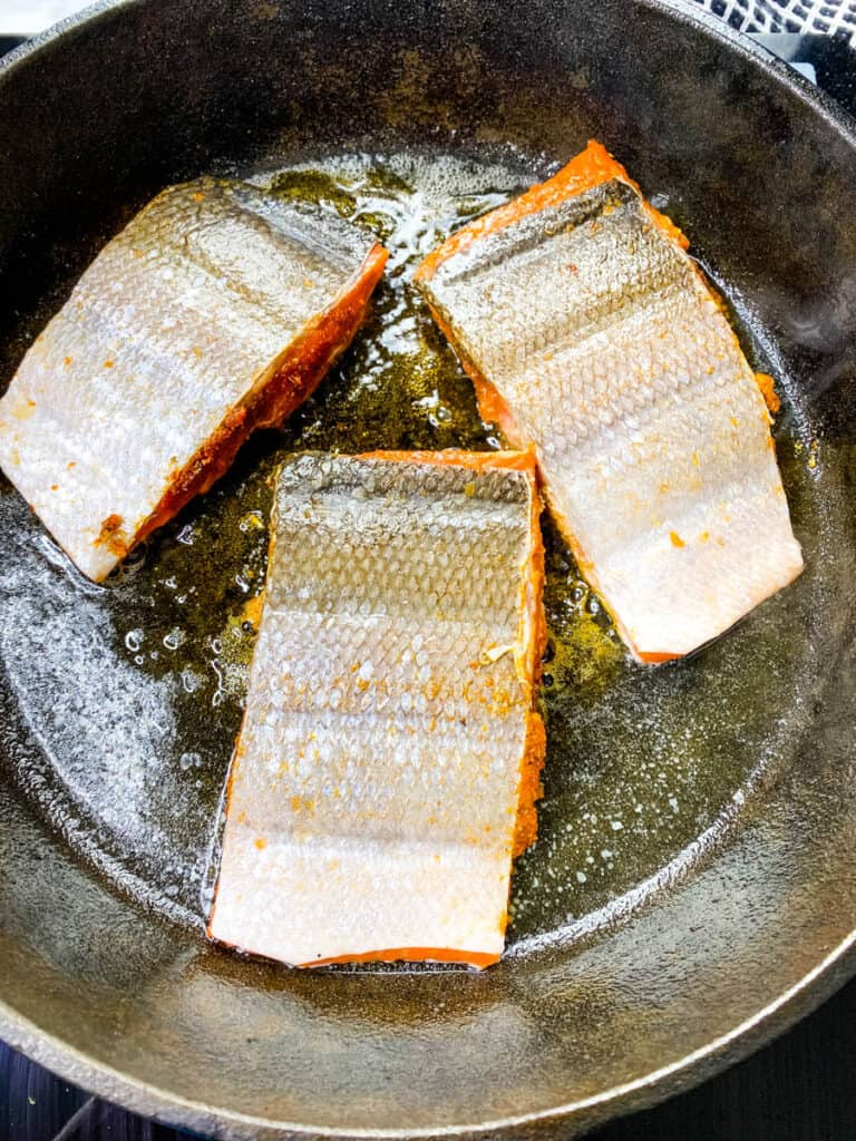 blackened salmon with the skin on cooking in a cast iron skillet