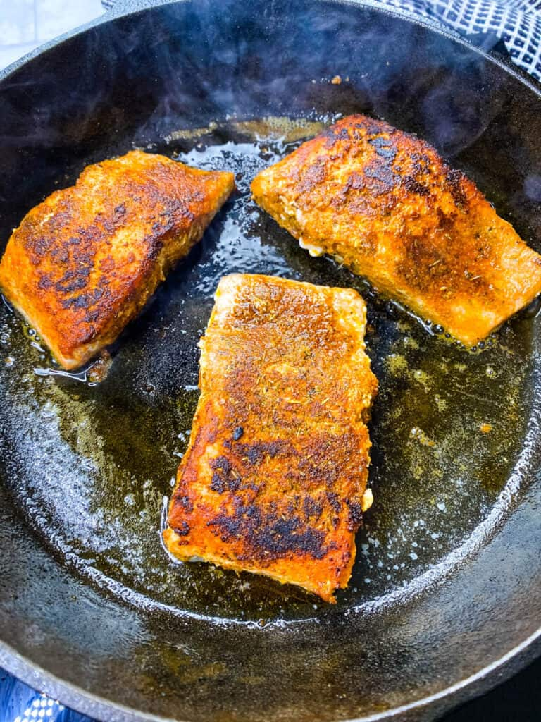 blackened salmon cooking in a cast iron skillet
