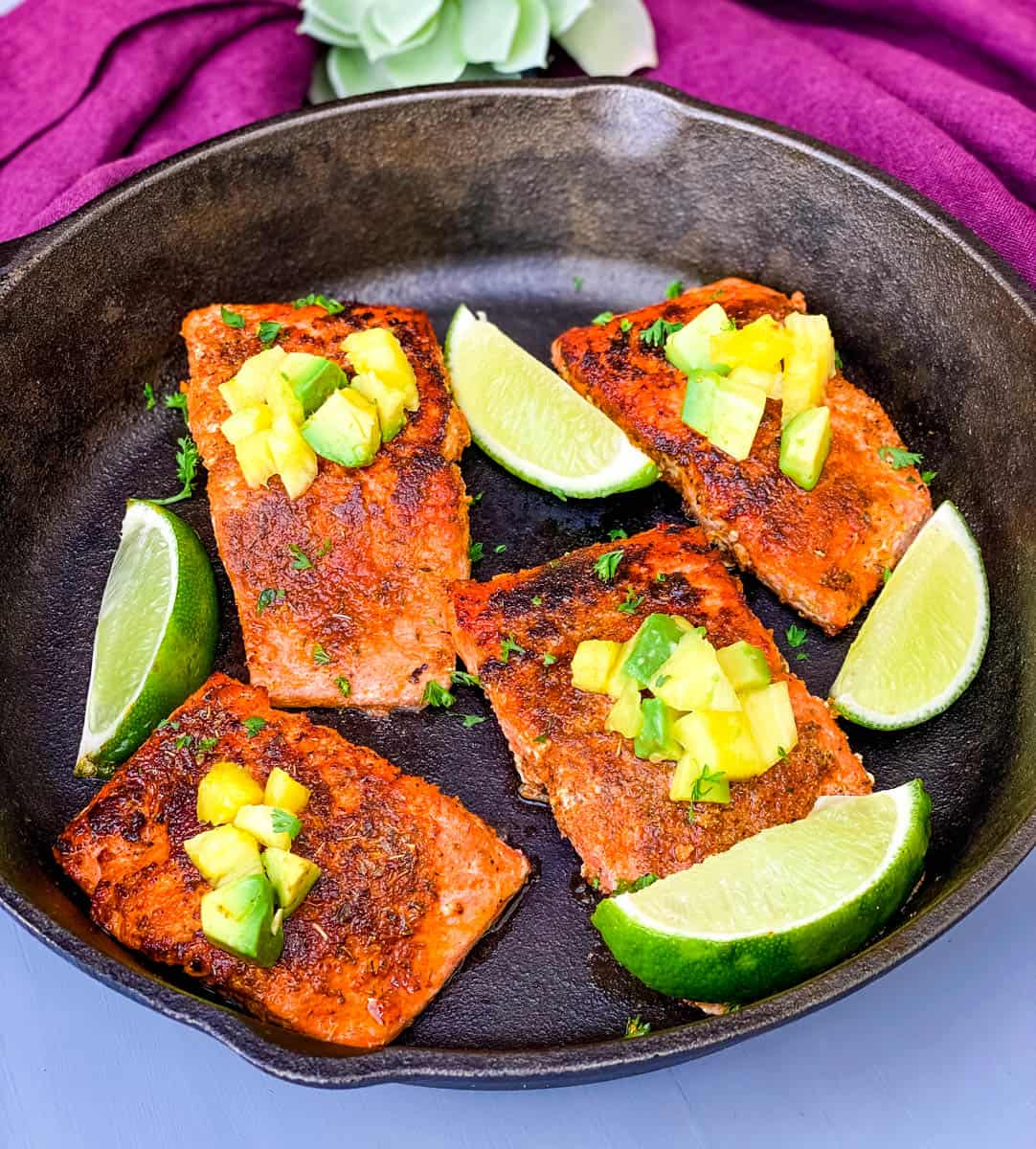 blackened salmon in a cast iron skillet topped with pineapple and avocado