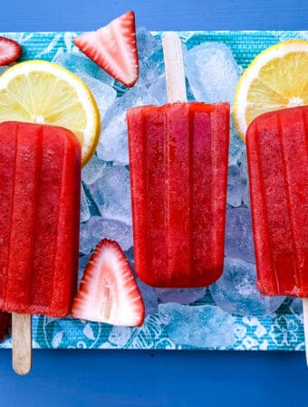 sugar free strawberry lemon popsicles on a flat surface with ice, fresh lemons and strawberries