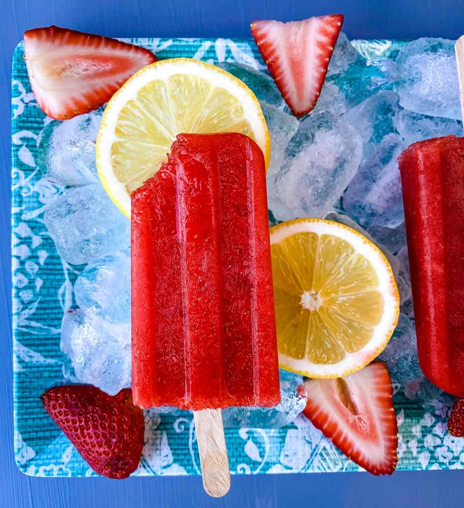 sugar free strawberry lemon popsicle with a bite removed on a flat surface with ice, fresh lemons and strawberries