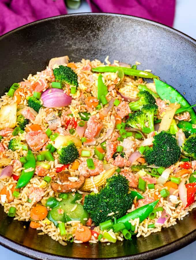 salmon fried rice with vegetables in a cast iron wok