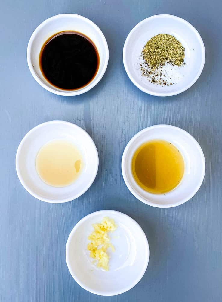 soy sauce, fish sauce, garlic, and seasoning in separate small white bowls