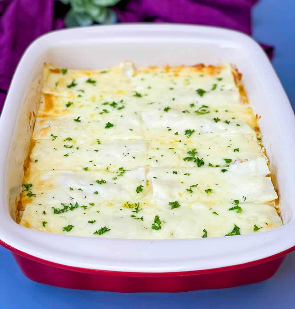 seafood lasagna in a red baking dish