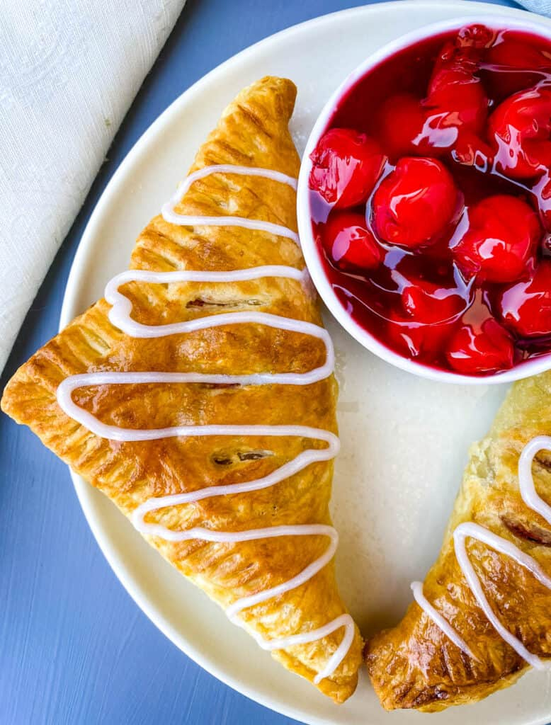 air fryer turnovers on a white plate with a bowl of cherries
