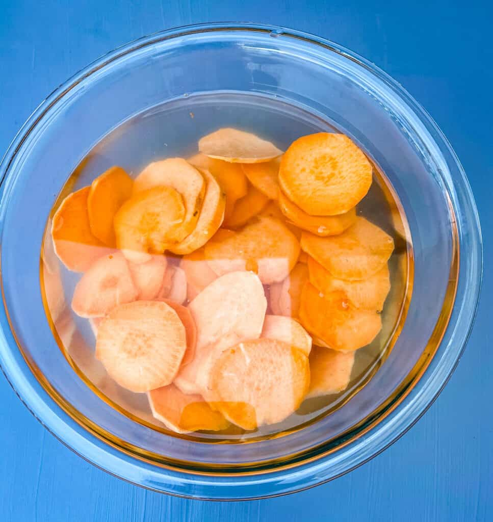 raw sliced sweet potato chips in a glass bowl with water