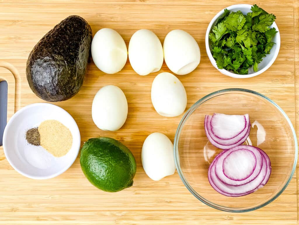hard boiled eggs, avocado, red onions, and cilantro on a flat surface