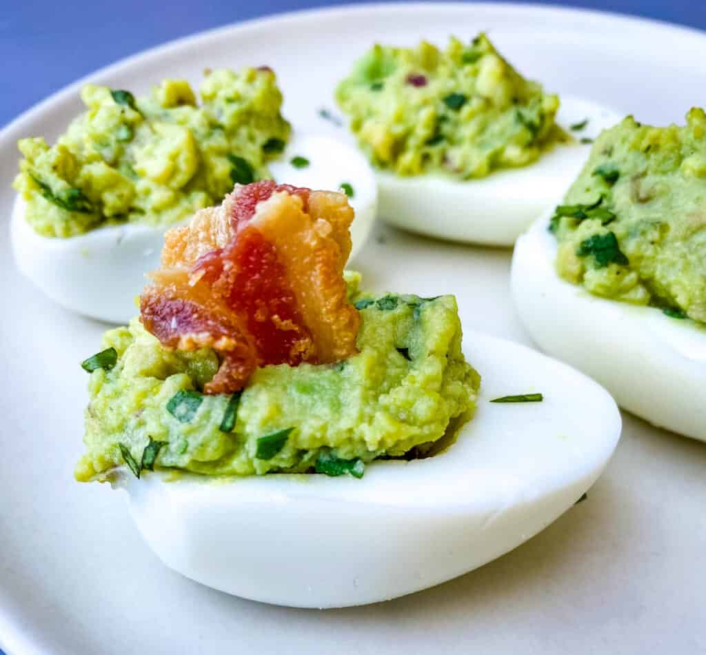 avocado deviled eggs with bacon on a