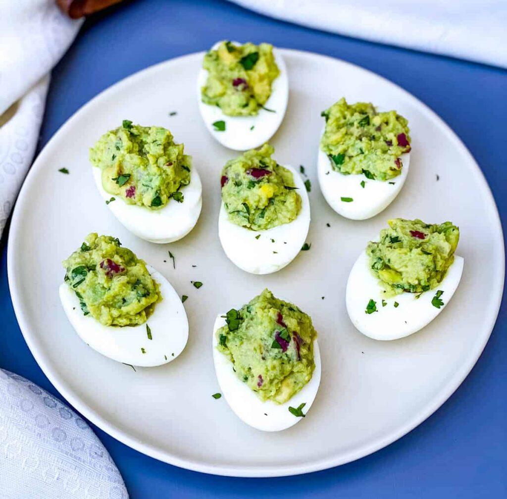 avocado deviled eggs on a white plate