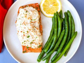 crab stuffed salmon on a plate with green beans and lemon