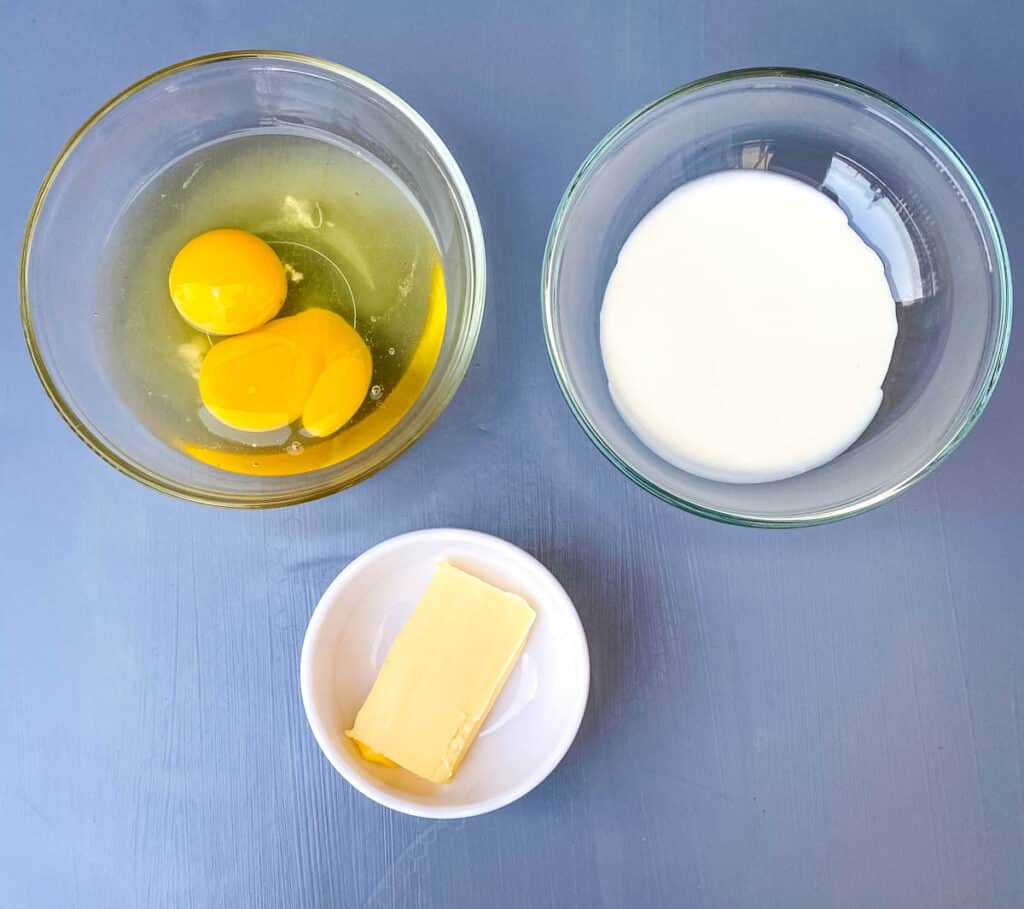 raw eggs, heavy cream, and butter in separate bowls