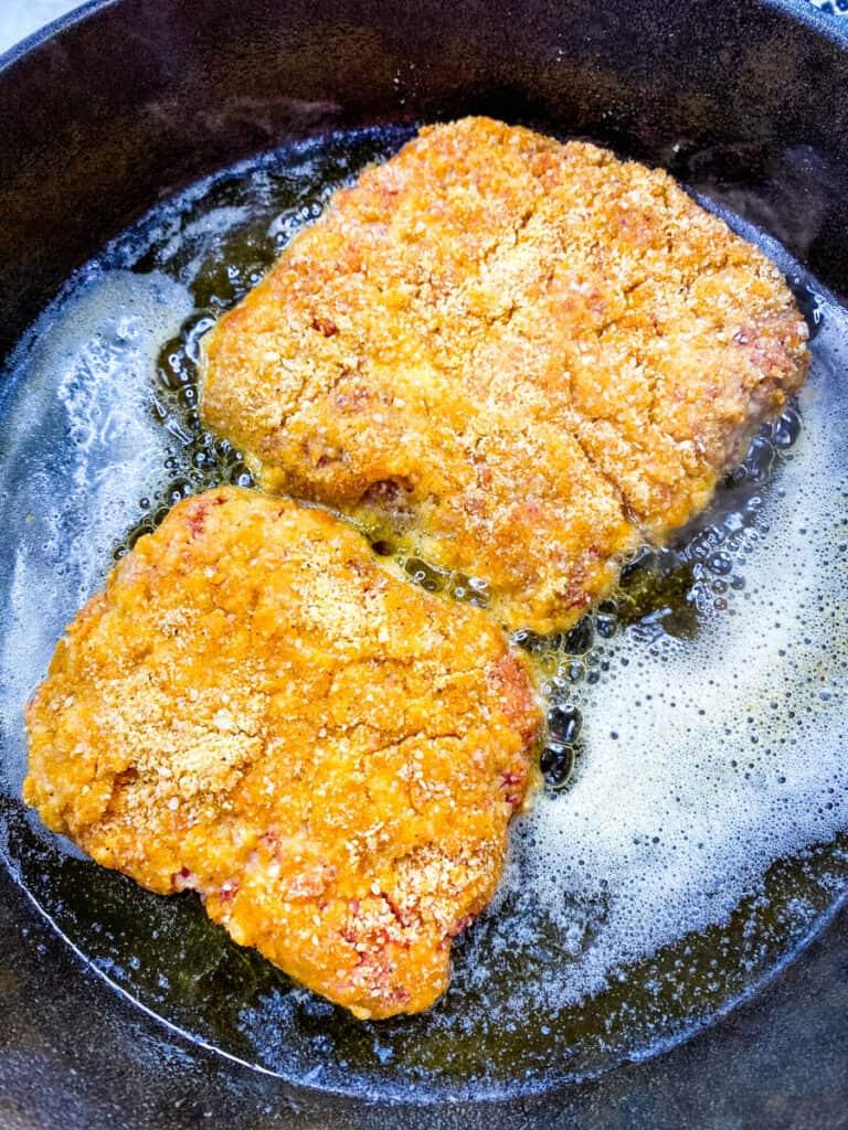 keto chicken fried steak fried in a cast iron skillet