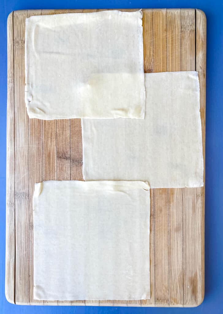 egg roll wrappers on a cutting board