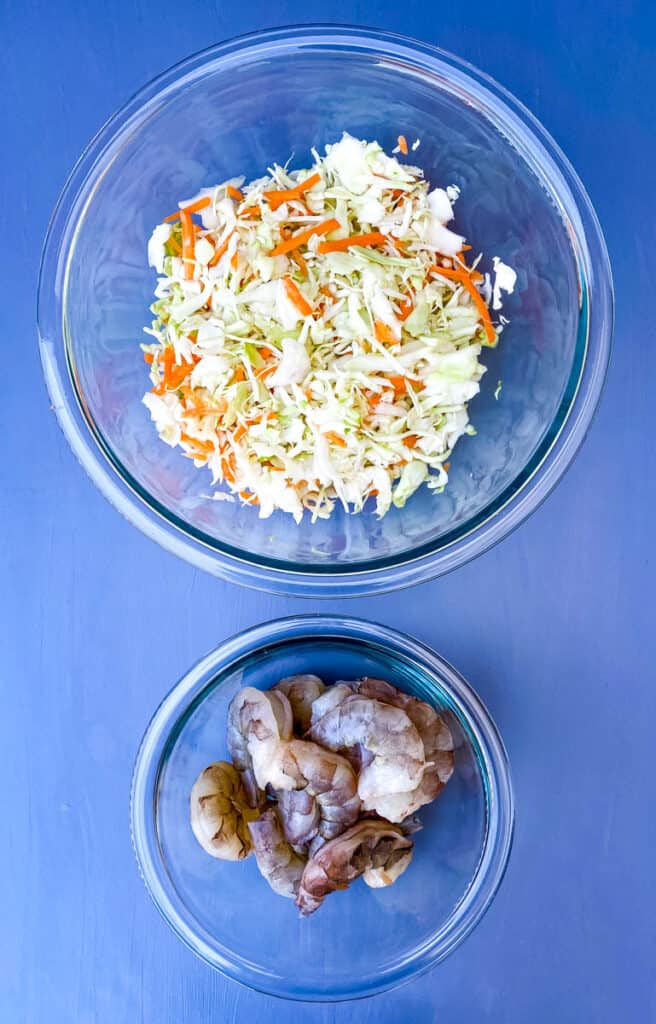 coleslaw mix and raw shrimp in seperate bowls