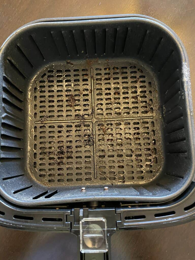 a dirty air fryer basket on a flat surface
