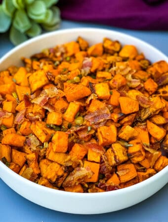 air fryer sweet potato hash with chopped bacon in a white bowl