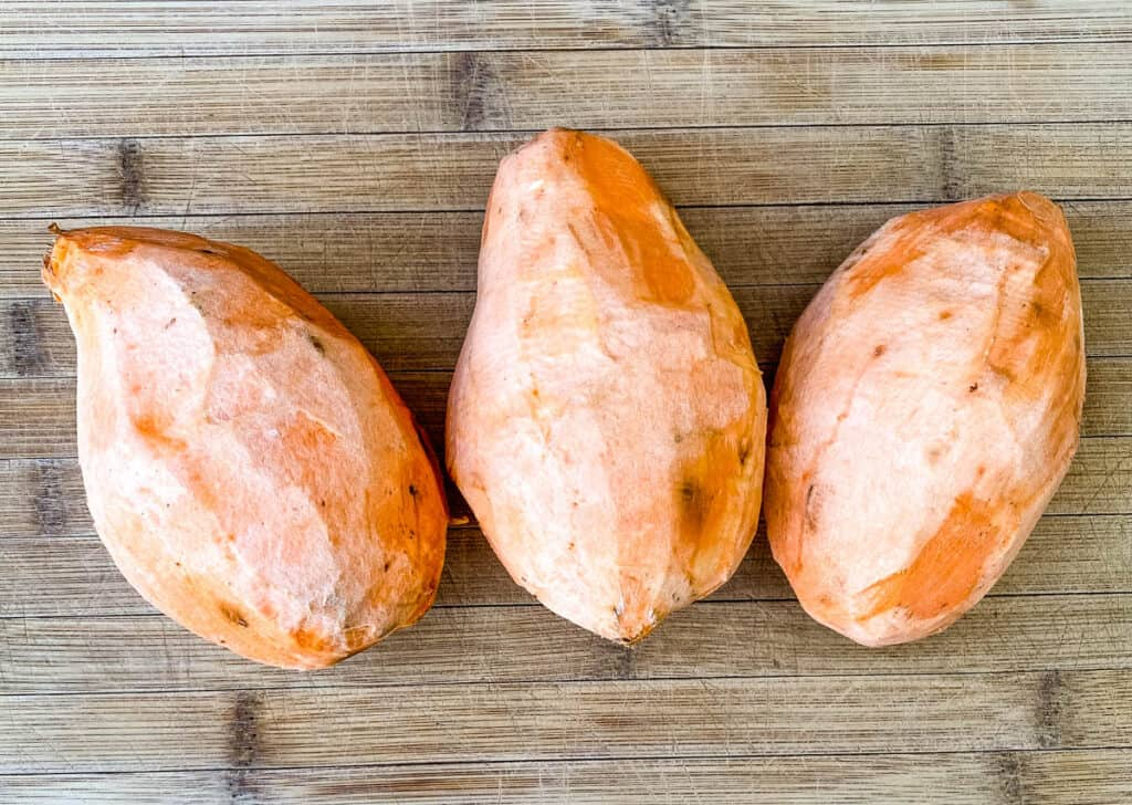raw sweet potatoes on a bamboo cutting board