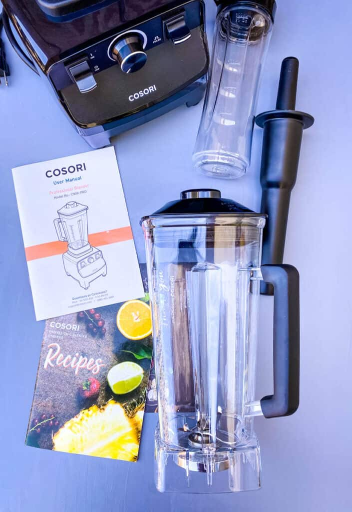 Cosori professional blender and travel cup on a flat surface