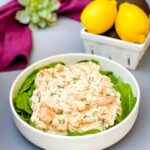 seafood crab salad with shrimp in a white bowl with spinach and a bowl of lemons