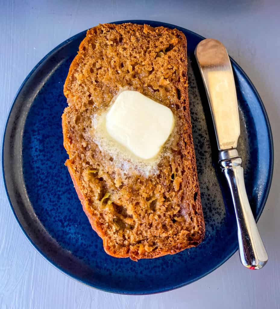 a slice of healthy banana bread on a blue plate with butter