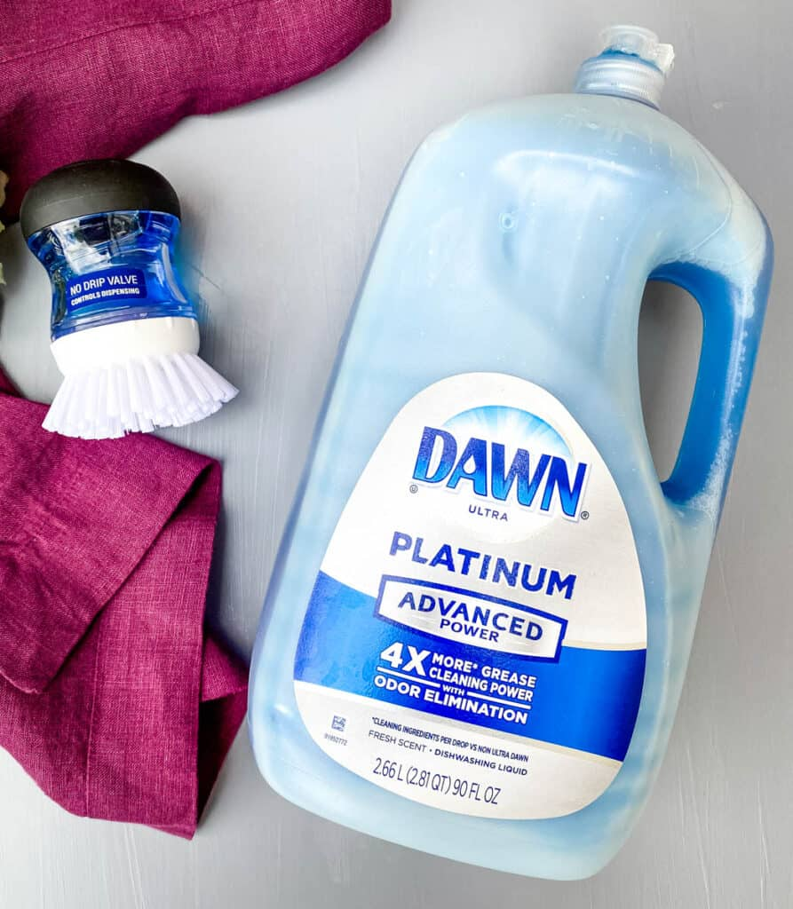 Dish washing liquid and a cleaning brush on a flat surface