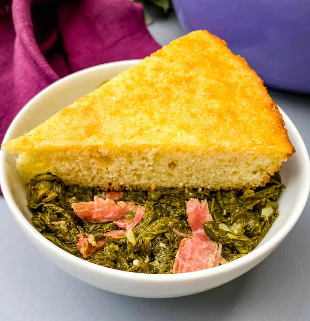 a bowl of southern mustard greens with smoked turkey and a slice of cornbread