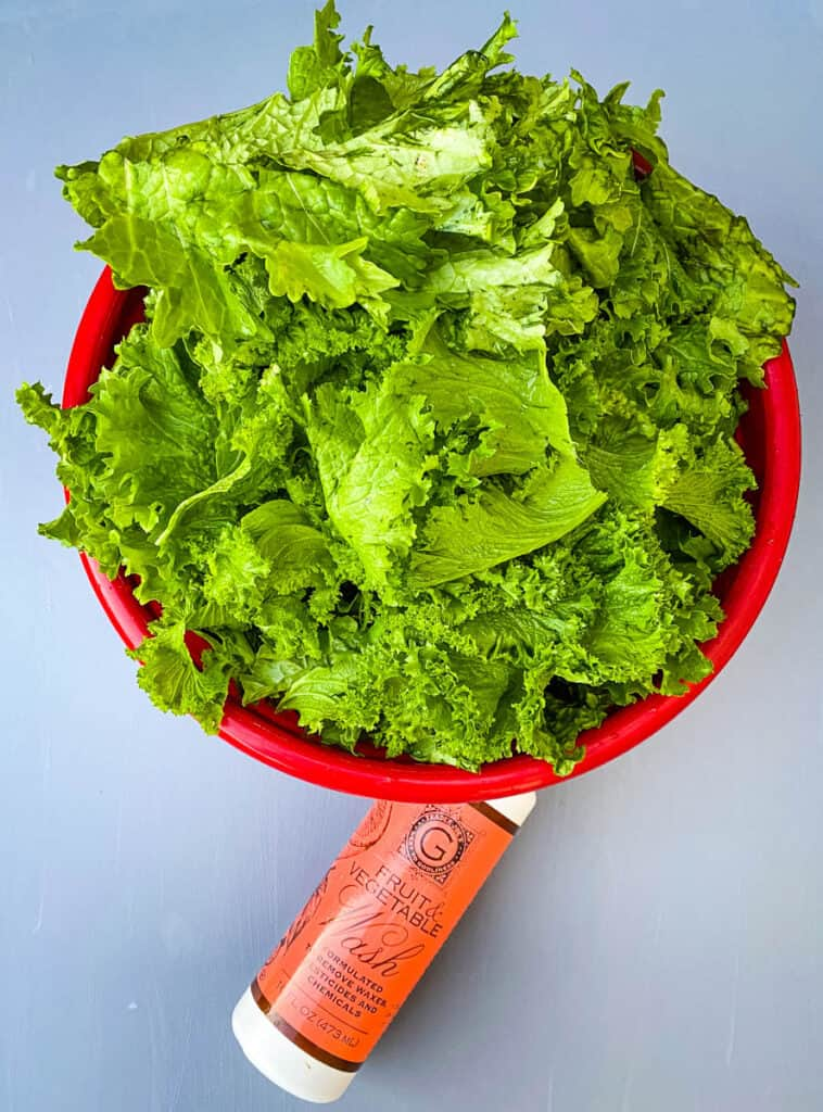 raw and fresh mustard greens in a red bowl with a bottle of produce cleaner
