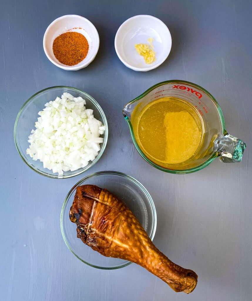 Creole seasoning, garlic, chopped onions, chicken broth, and smoked turkey on a flat surface