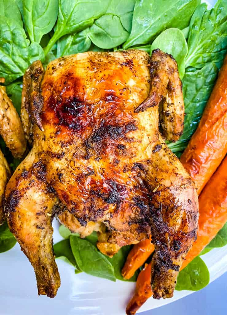 air fryer Cornish hens, fresh spinach, and carrots on a white plate
