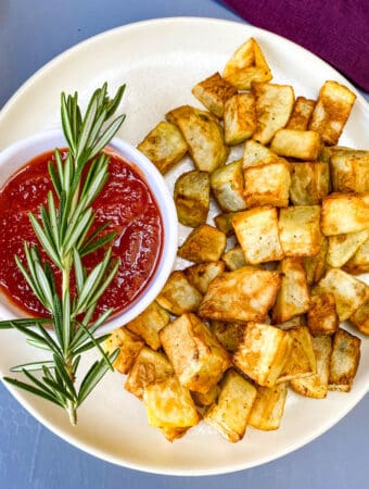 air fryer roasted potatoes on a white plate with ketchup