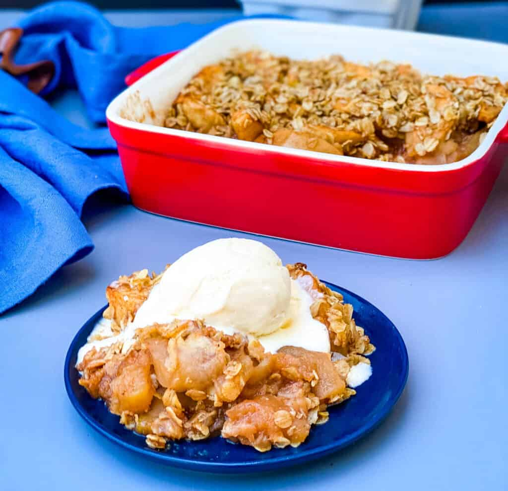 healthy apple crisp on a plate with a scoop of vanilla ice cream with a baking dish of crisp