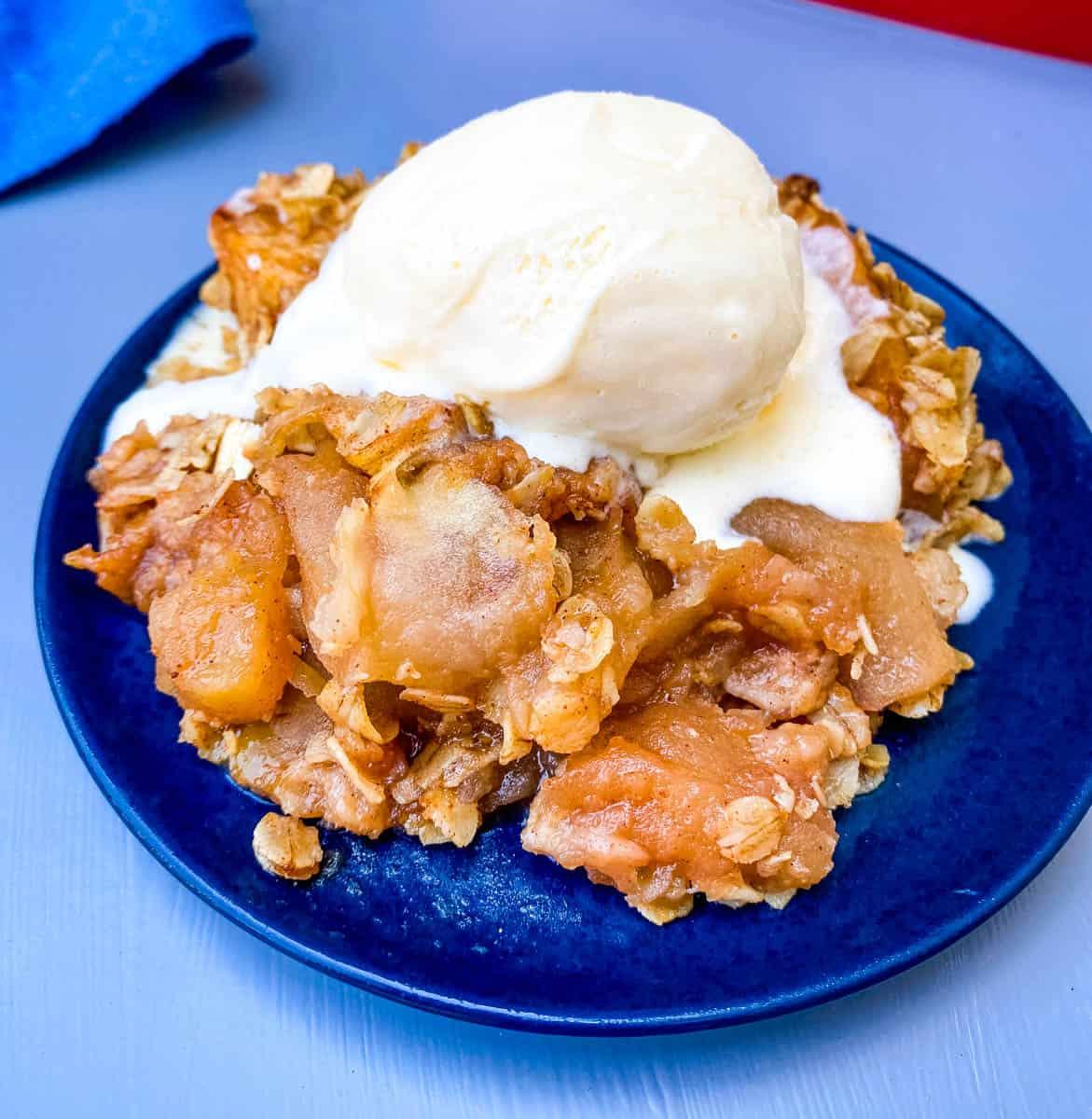 healthy apple crisp on a blue plate with vanilla ice cream